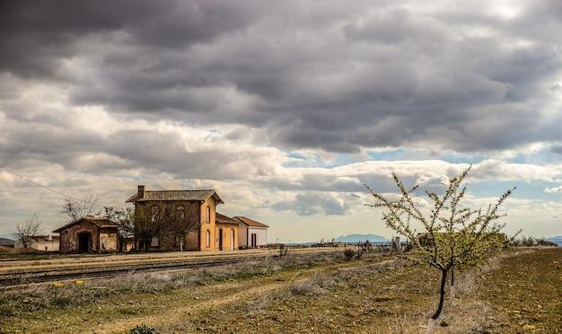 Disparo de gran angular de casas antiguas en un campo verde bajo un cielo nublado