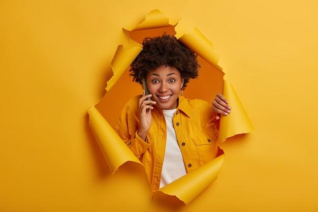 Disparo horizontal de alegre mujer afroamericana tiene conversación por teléfono celular, charla alegremente