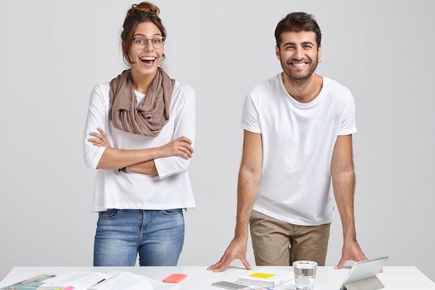 Disparo horizontal de alegre mujer europea con los brazos cruzados, mirada emocionada, viste un traje de moda, reacciona ante el buen resultado del trabajo del proyecto, se encuentra junto al socio comercial