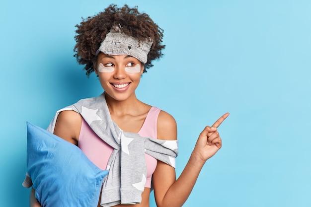 Disparo horizontal de alegre niña étnica en ropa de dormir sonríe positivamente indica en la esquina superior derecha sostiene la almohada demuestra producto para descansar aislado sobre pared azul