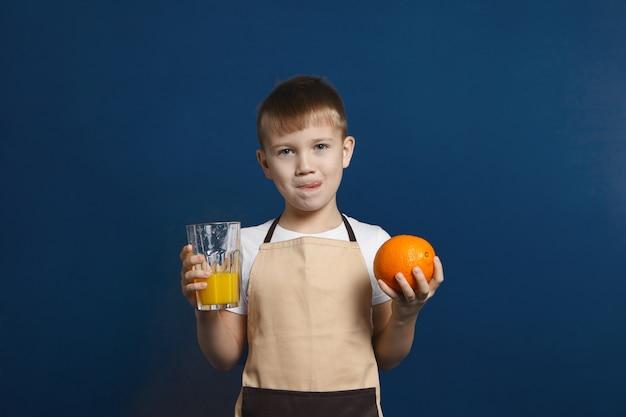 Disparo horizontal de alegre niño europeo en delantal beige lamiendo los labios como signo de placer mientras toma jugo de cítricos fresco