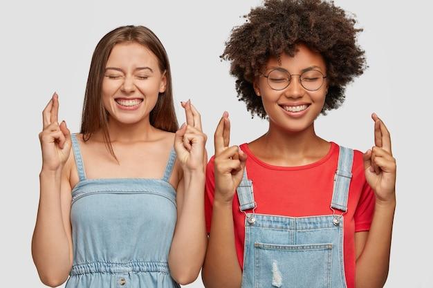 Disparo horizontal de alegres mujeres jóvenes diversas hacen gesto de deseo