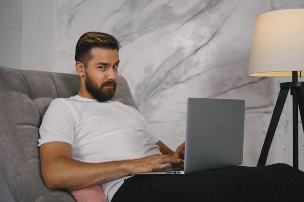 Disparo horizontal de apuesto joven barbudo con camiseta blanca mirando a la cámara, con expresión facial sospechosa, navegar por noticias, blog de videos o chatear en línea usando una computadora portátil genérica