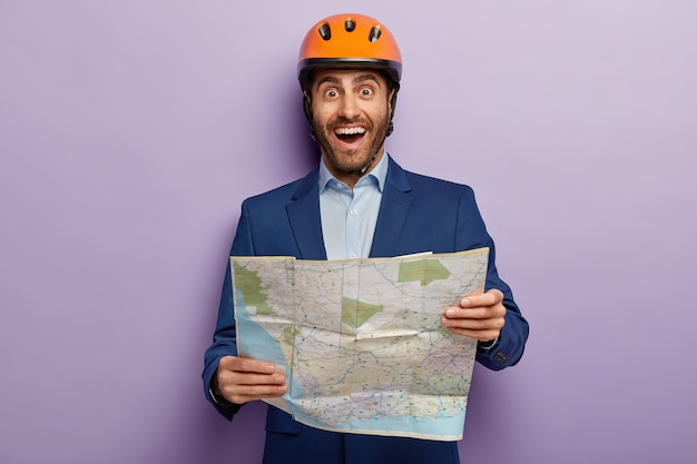 Disparo horizontal de arquitecto masculino feliz con mapa, mapa de ubicación de estudios donde se encuentra el sitio de construcción, usa helemt protector, ropa formal