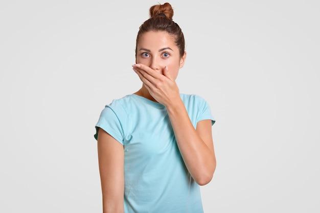 El disparo horizontal de la atractiva joven sorprendida cubre la boca con la palma de la mano, vestido con una camiseta azul casual, intenta quedarse sin palabras, posa contra la pared blanca, expresa asombro. concepto de omg