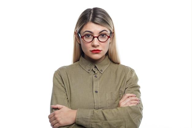 Disparo horizontal de atractiva mujer joven con cabello rubio suelto y labios rojos manteniendo los brazos cruzados, su mirada y postura expresan desagrado o desacuerdo sobre alguna decisión o idea comercial