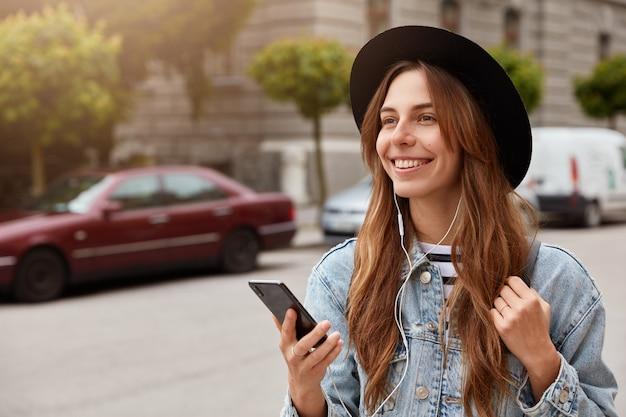 Disparo horizontal de chica alegre con sombrero de moda, pasa tiempo libre al aire libre