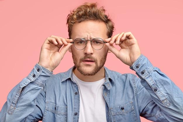 Disparo horizontal de chico de aspecto agradable mira escrupulosamente a través de gafas, intenta notar algo