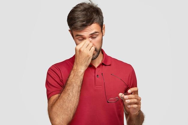 Disparo horizontal de un chico guapo con exceso de trabajo mantiene la mano en la nariz, se quita las gafas, siente dolor en los ojos después del trabajo en la computadora, quiere dormir, usa una camiseta roja informal, aislado sobre una pared blanca