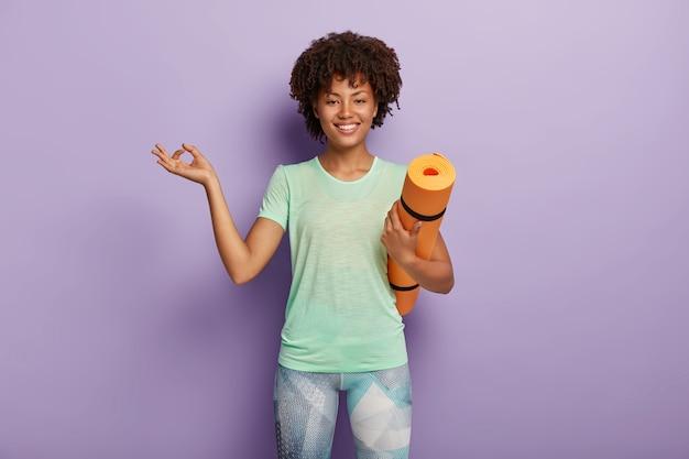 Disparo horizontal de complacida mujer sana de piel oscura medita, tiene ejercicios de yoga, lleva colchoneta de fitness