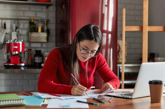 Disparo horizontal de empresaria de aspecto agradable trabaja con papeles en casa, prepara el documento del informe, completa la información, se sienta frente a la computadora portátil abierta en la cocina.