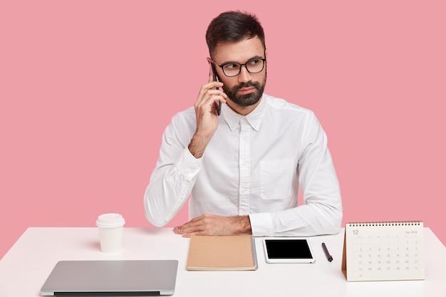 Disparo horizontal de empresario serio tiene cerdas gruesas, conversación telefónica, enfocado en la distancia, vestido con ropa formal, tiene orden en el escritorio