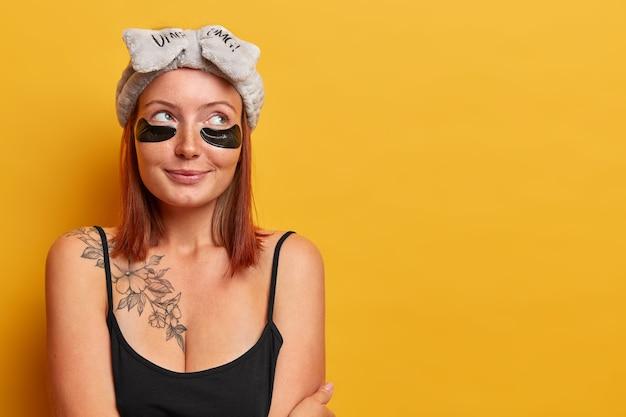 Disparo horizontal de una hermosa mujer adulta vestida con una camiseta negra sin mangas, tiene un tatuaje en el cuerpo, mira hacia otro lado con expresión pensativa, usa una diadema y parches de hidrogel, se preocupa por la piel y la belleza