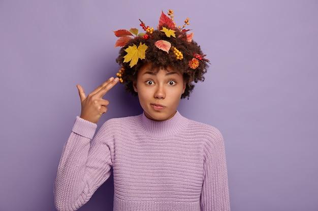 Disparo horizontal de una hermosa mujer afroamericana desconcertada dispara en la sien con los dedos, muestra un gesto de suicidio, vestida con un suéter cálido, como hojas amarillas en el cabello