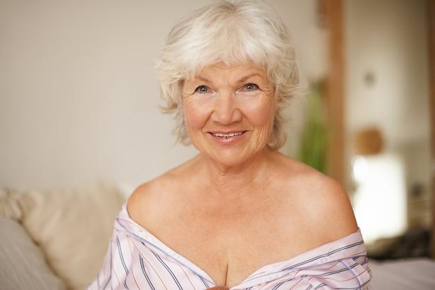 Disparo horizontal de hermosa mujer de pelo gris positiva con arrugas y hombros desnudos sentada en el acogedor interior del dormitorio con camisón a rayas, mirando con una sonrisa feliz y coqueta