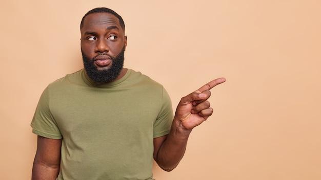 Disparo horizontal de un hombre adulto serio en ropa casual apunta el dedo índice a un lado en el espacio de copia la dirección de gies recomienda espacio de copia para poses publicitarias contra la pared marrón