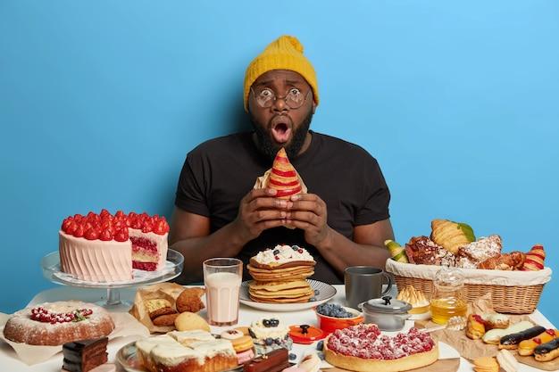 Disparo horizontal de hombre sin afeitar sostiene croissant, tiene expresión facial estupefacta, conmoción por tener adicción al azúcar, usa sombrero amarillo, camiseta y gafas, mira con estupor.