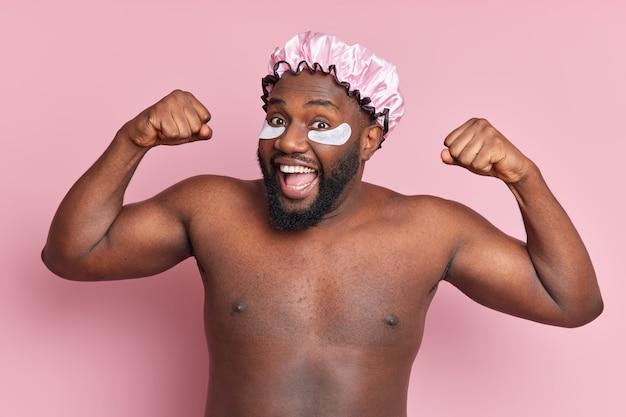 Disparo horizontal de un hombre barbudo positivo que se prepara para tomar una ducha, levanta los brazos, muestra el bíceps, se siente divertido, usa un sombrero impermeable, aplica almohadillas de colágeno debajo de los ojos, está sin camisa en el interior