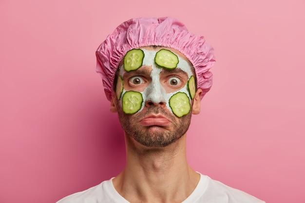 Disparo horizontal de hombre infeliz recibe tratamientos de cosmetología, refresca la piel con mascarilla vegetal, mira fijamente a la cámara, usa gorro de baño