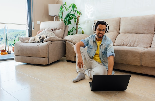 Disparo horizontal de un hombre sentado en el suelo escuchando música y trabajando con un portátil en casa