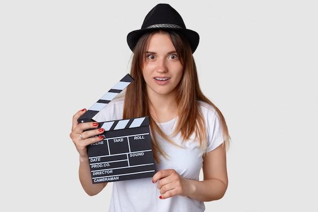 Disparo horizontal de la joven y bella productora de cine sorprendida sostiene tablilla de la película