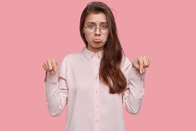 Disparo horizontal de una joven disgustada que tiene una expresión facial sombría, apunta al piso con ambos dedos índices, siente disgusto