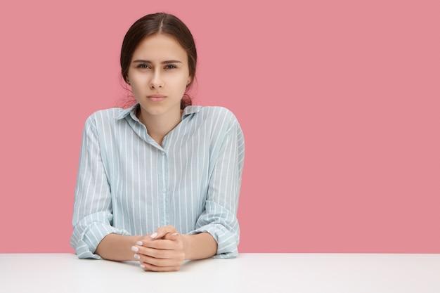 Disparo horizontal de joven gerente frustrada que tiene un mal día en el trabajo. mujer seria experta en recursos humanos realizando una entrevista de trabajo, con una expresión estricta posando aislado