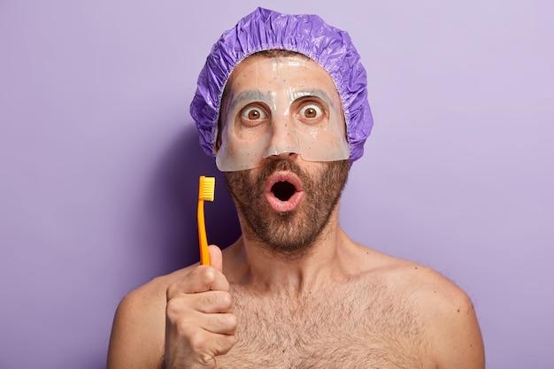 Disparo horizontal de joven recibe asesoramiento de cosmetóloga profesional, aplica mascarilla de belleza para piel suave en la cara, va a cepillarse los dientes, sostiene el cepillo de dientes