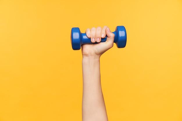 Disparo horizontal de mano femenina levantada mientras realiza ejercicios físicos con agente de ponderación, aislado sobre fondo amarillo. concepto de fitness y pérdida de peso