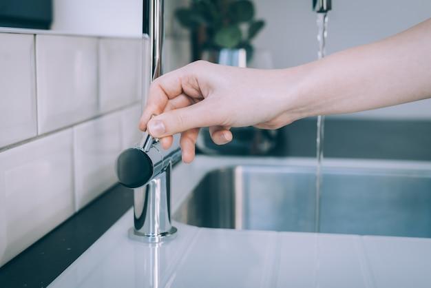 Disparo horizontal de una mano humana abriendo el fregadero moderno para el flujo de agua