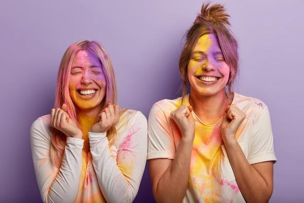 Disparo horizontal de mejores amigas llenas de alegría, apretar los puños con triunfo, celebrar el festival de holi en la india, jugar con polvos coloridos, ropa informal manchada de blanco celebración de la primavera que viene