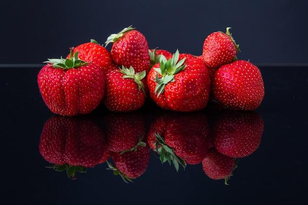 Disparo horizontal de un montón de fresas croatas rojas sobre una superficie reflectante negra