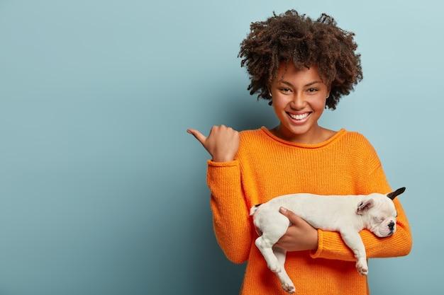 Disparo horizontal de una mujer afro complacida que señala el espacio libre, muestra la dirección a la tienda de mascotas, compró un cachorro de pedigrí, tiene una sonrisa agradable en los modelos faciales sobre una pared azul. amor entre perro y dueño