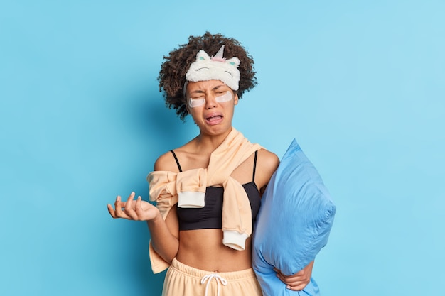 Disparo horizontal de una mujer afroamericana abatida llora de desesperación vestida con ropa de dormir sostiene una almohada sufre insomnio aplica parches de colágeno aislados sobre una pared azul