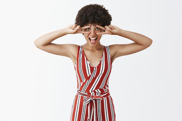 Disparo horizontal de mujer afroamericana joven atractiva, feliz y emocionada expresiva con peinado afro en monos a rayas que muestran gestos de victoria o discoteca sobre los ojos y sonriendo ampliamente