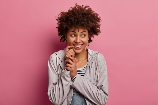 Disparo horizontal de una mujer afroamericana de pelo bastante rizado que se ve positivamente a un lado, tiene una sonrisa tierna, usa un anorak casual, mira hacia otro lado con alegría, está de buen humor, aislado en la pared rosa
