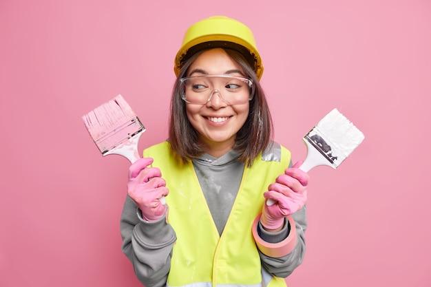 Disparo horizontal de mujer asiática sostiene herramientas de construcción se siente muy feliz después de terminar la renovación de la casa usa ropa de seguridad