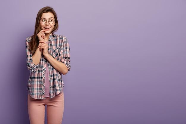 Disparo horizontal de mujer complacida con apariencia europea, tiene una sonrisa suave en la cara, mira hacia otro lado, usa gafas ópticas
