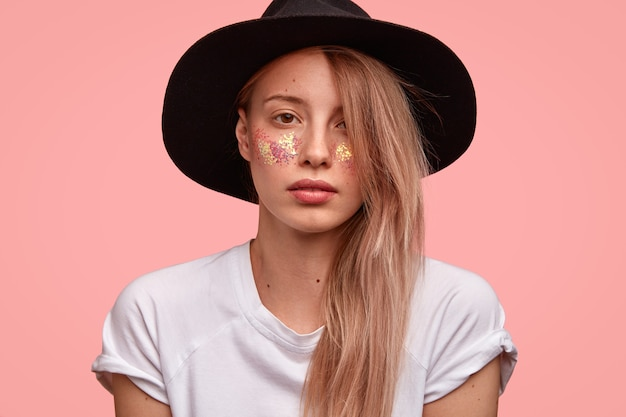 Disparo horizontal de una mujer europea de aspecto agradable que tiene destellos en las mejillas, viste un sombrero negro y una camiseta blanca informal, se ve con confianza, muestra su belleza, aislada sobre una pared rosa