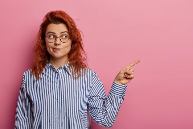 Disparo horizontal de la mujer europea de jengibre frunce los labios y demuestra algo en el espacio en blanco, señala el dedo índice a un lado