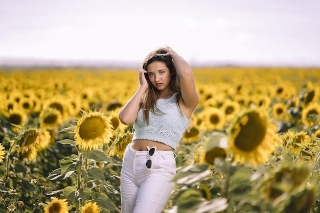 Disparo horizontal de una mujer joven caucásica posando en un brillante campo de girasoles en un día soleado