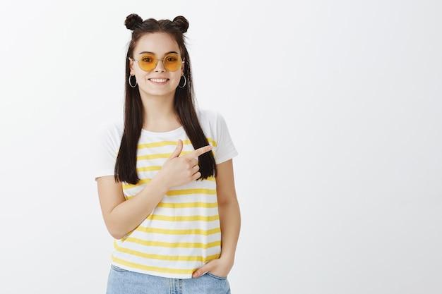 Disparo horizontal de mujer joven despreocupada posando con gafas de sol contra la pared blanca