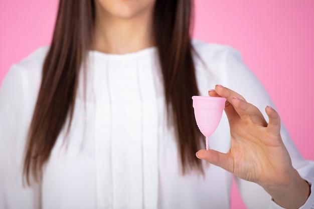 Disparo horizontal de mujer morena sosteniendo en la mano copa menstrual de plástico aislado sobre rosa