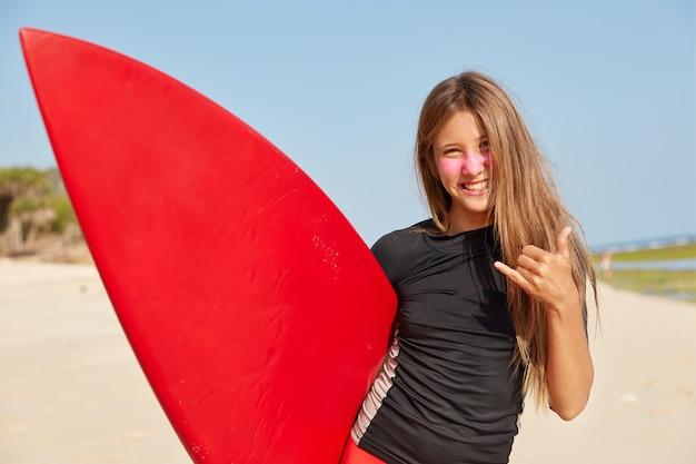 Disparo horizontal de niña feliz disfruta de buenas condiciones climáticas para surfear, hace shaka o gesto suelto