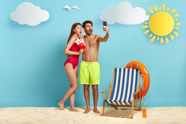 Disparo horizontal de una pareja masculina y femenina sorprendida que disfruta de pasar las vacaciones de verano en el lugar del resort, mostrar el pasaporte con boletos de embarque en la cámara del teléfono celular y hacer selfie en la playa sobre fondo azul