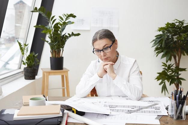 Disparo horizontal de pensativa ingeniera de mediana edad con gafas negras y camisa blanca con las manos juntas debajo de la barbilla, estudiando dibujos y especificaciones en el escritorio frente a ella