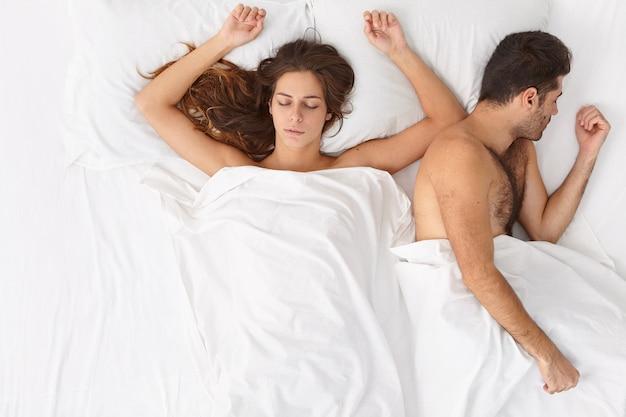 Disparo horizontal de relajado hombre y mujer casada que permanecen juntos en la cama, disfrutan de una mañana acogedora e intimidad, tienen un sueño saludable, descansan después del sexo apasionado, se acuestan bajo sábanas blancas. buenas noches, duerme