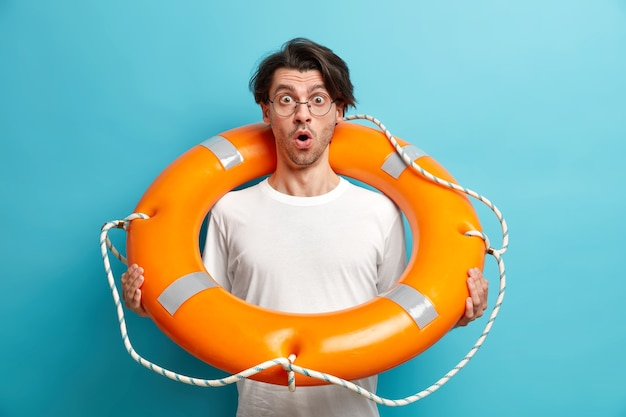 Disparo horizontal del socorrista de playa joven sorprendido plantea salvavidas inflado mantiene la boca abierta