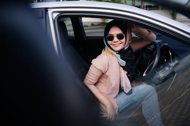 Disparo interior de un coche con una mujer sentada con los ojos cerrados en el asiento trasero.