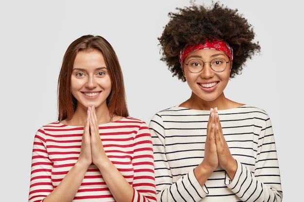 Disparo en interiores de encantadoras estudiantes interraciales alegres que mantienen las manos en gesto de oración, piden buena suerte antes del examen, usan suéteres a rayas casuales, se paran una al lado de la otra aisladas sobre una pared blanca